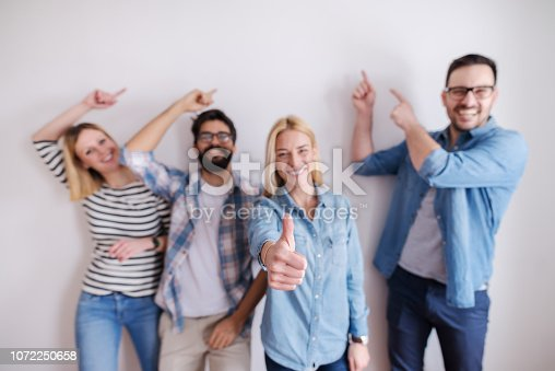 istock Small group of people pointing on the wall and one girl gives thumbs up. Start up business concept. 1072250658