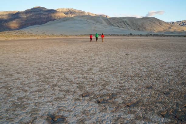 A small group of people walk across a desert playa towards sand dunes stock photo