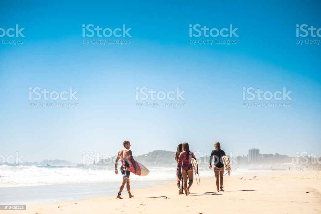 Small group of people walking on the beach with their surfboards stock photo