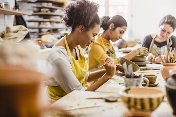 pequeño grupo de jóvenes, creación de cerámica - clase de arte fotografías e imágenes de stock