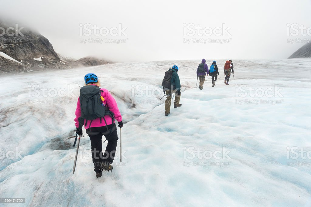 Small group treks over glacier ice stock photo