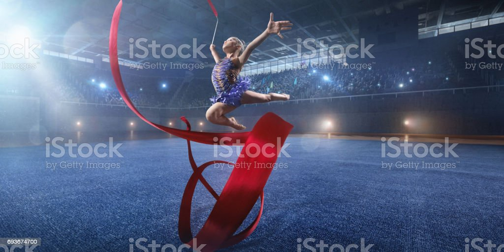 A small gymnast girl makes performance with gymnastic band on a large professional stage stock photo