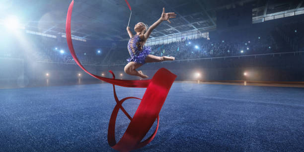Eine kleine Turnerin Mädchen macht Leistung mit Gymnastik Band auf einer großen professionellen Bühne – Foto