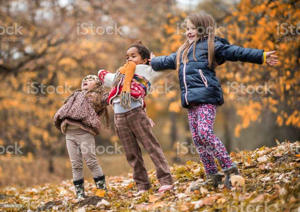 Small happy girls having fun in autumn day. stock photo