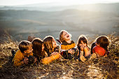Small happy kids having fun while relaxing in autumn day on a hill.