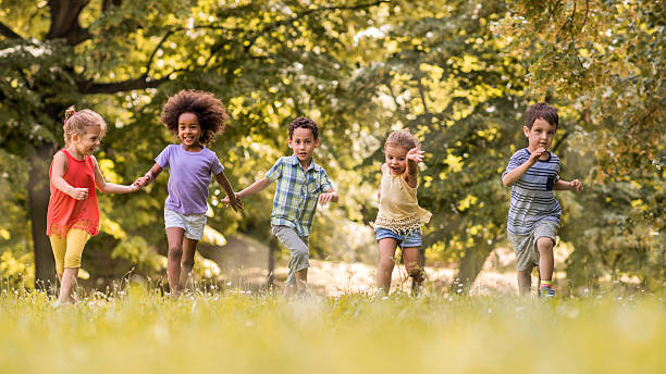 Small happy kids having fun while running in nature. stock photo