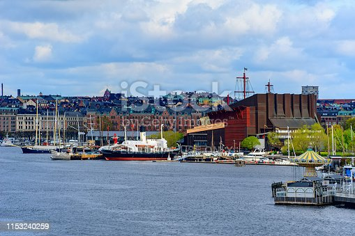 STOCKHOLM, SWEDEN - May 03, 2019: Small harbour on the south side of Djurgarden island with moored museum ships and Vasa Museum, displaying recovered Vasa warship built in 17th century.