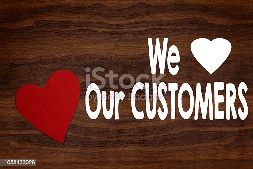 istock small heart paper on wood table, We love our customers concept 1058433026