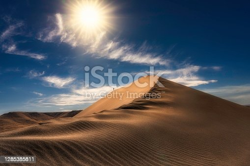 istock small hiker in distance on epic sand dune landscape 1285385811