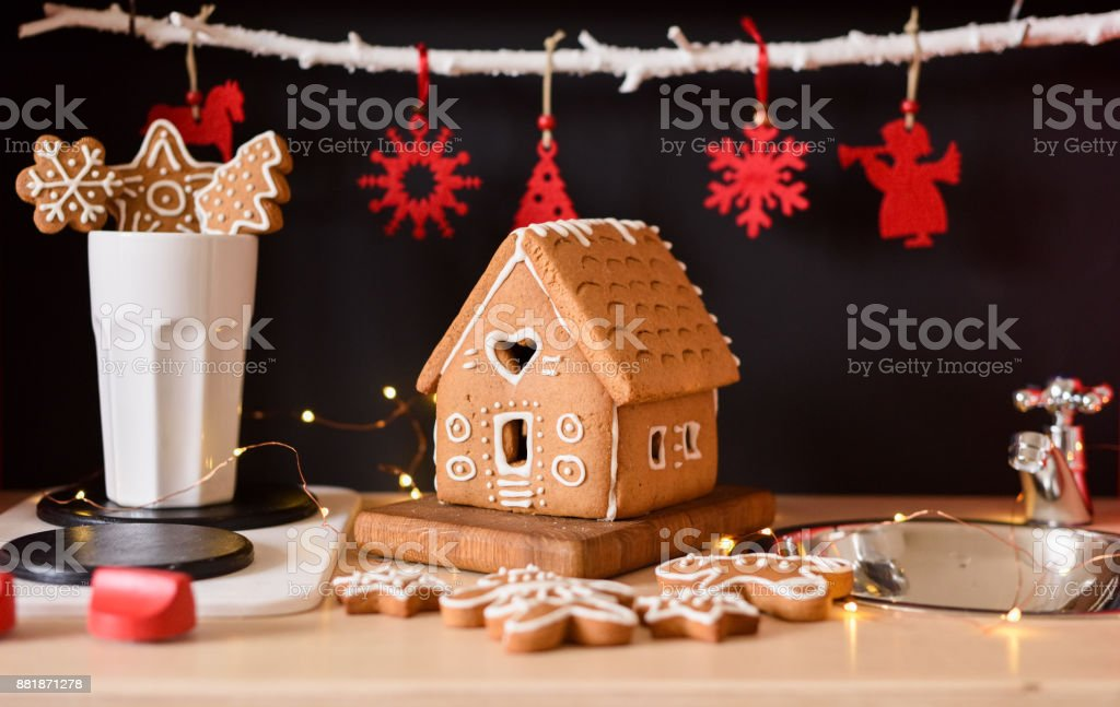 Small homemade gingerbread house, cookies and red Christmas toys on black background in toy kitchen stock photo