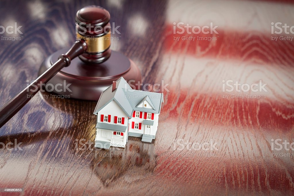 Small House and Gavel on Table with American Flag Reflection stock photo