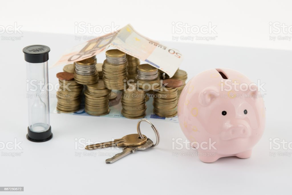 Small House and Piggy Bank with Stacks of money  Isolated on a White Background. stock photo