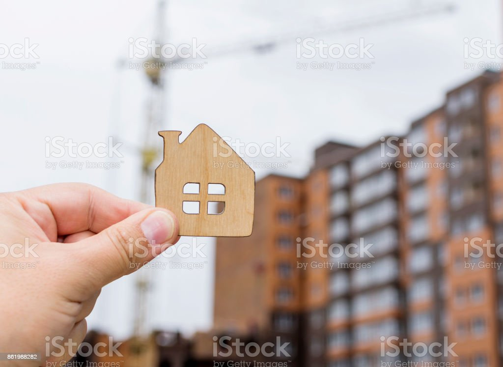 A small house in hand against the background of construction site. Selective focus. stock photo