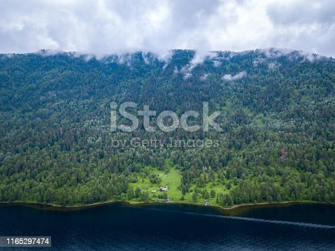 istock Small house in the Altai Mountains near the lake surrounded by green trees on a sunny summer day 1165297474