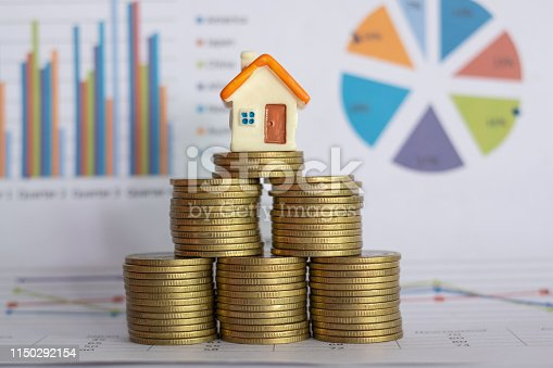 A small house on a pile of coins And have a financial chart.Mini house model and stack of coins. Business growth. Property investment and house mortgage financial real estate concept