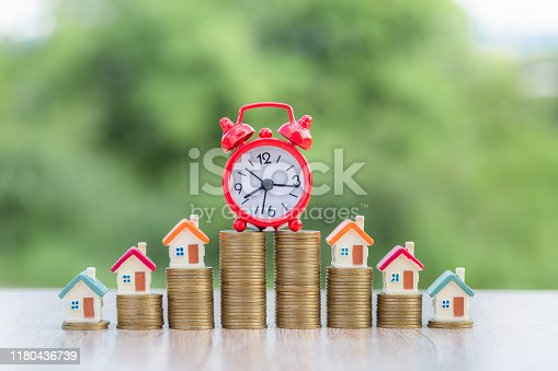 Small house on the coin ladder With a red alarm clock on the coin ladder. Investment concepts. Finance. Accounting. Stock market. Real estate. Mortgage. Using the time to make money to buy a house.