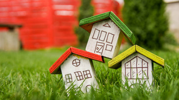 Small houses with color roofs over green and red fence stock photo