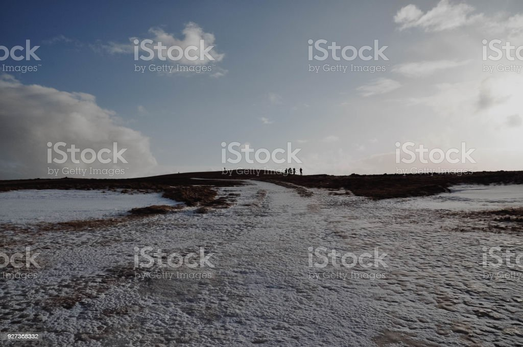 Small Humans in Iceland Landscape photo of humans at the top of a hill in Iceland Cloud - Sky Stock Photo