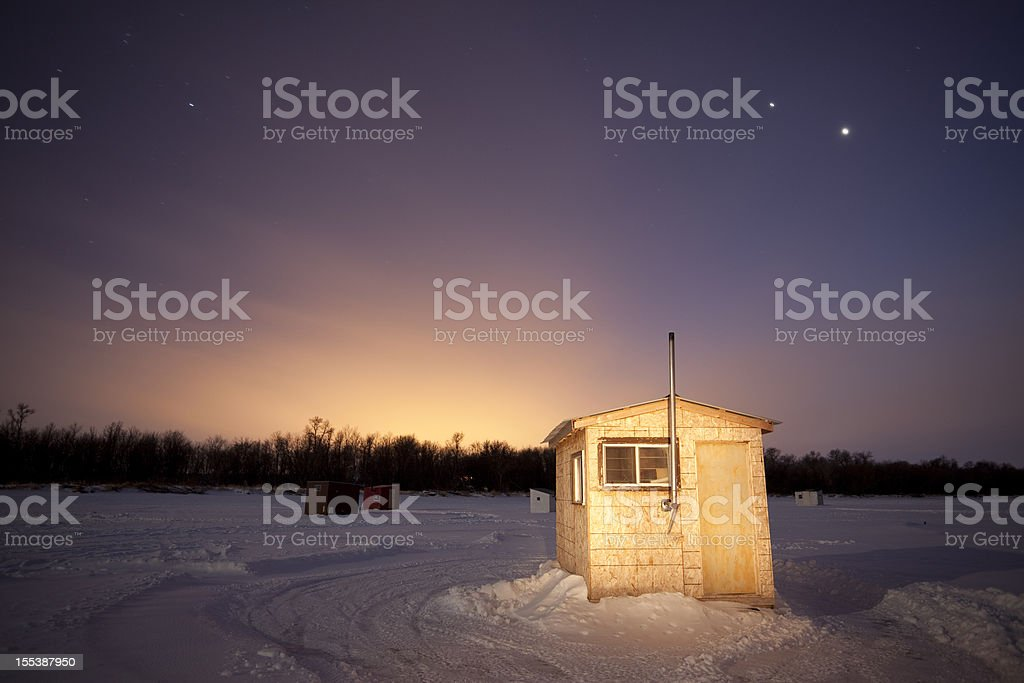 Small ice fishing huts at sunset stock photo