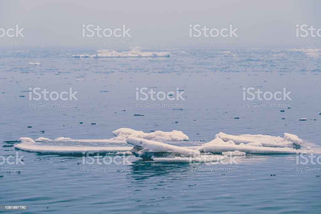 Small ice floe floats in the open sea in early winter stock photo
