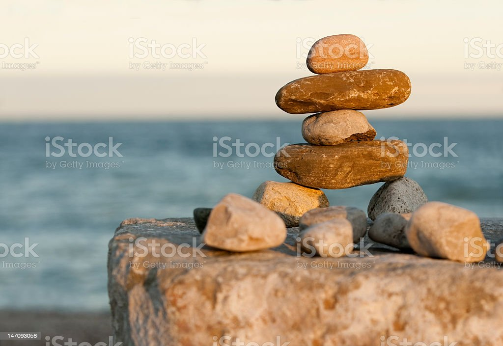 Small inukshuk made of stones by a body of water stock photo