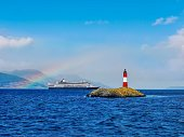 A picturesque scene, with a red and white lighthouse on a small rocky island in a tranquil, blue channel. A cruise ship in the background is framed by a partial rainbow, which is set against a vibrant blue sky with some fluffy clouds. This area is the gateway to Antarctica from southern Argentina.