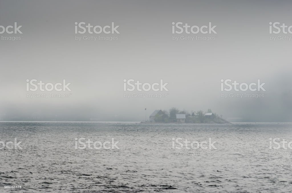 Small island with cottages in the St. Lawrence River surrounded by fog. royalty-free stock photo