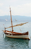 A small traditional Italian fishing boat, rigged for sail, at anchor in the Mediterranean at Portofino on the Ligurian coast