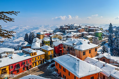 View from above of colorful houses of small italian town covered in snow in Piedmont, Northern Italy.
