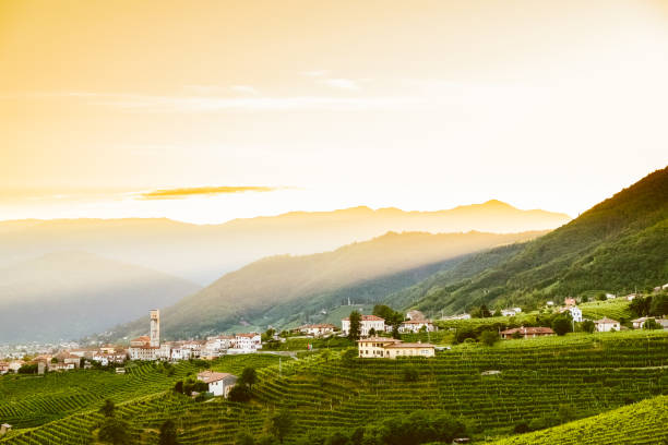 small italian town of valdobbiadene in veneto region on green hills at sunset with prosecco vineyards stock photo
