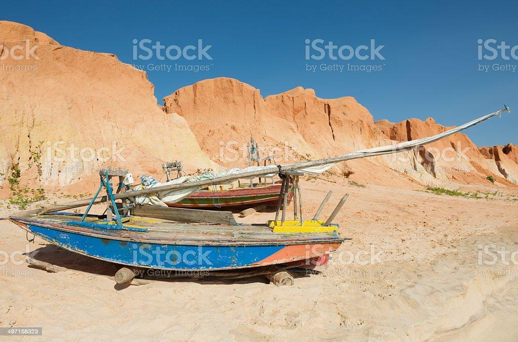 Small jangada fishing boats and red cliffs of Canoa Quebrada royalty-free stock photo