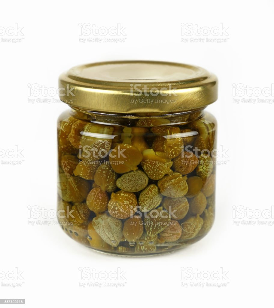 Small jar of pickled green capers over white stock photo
