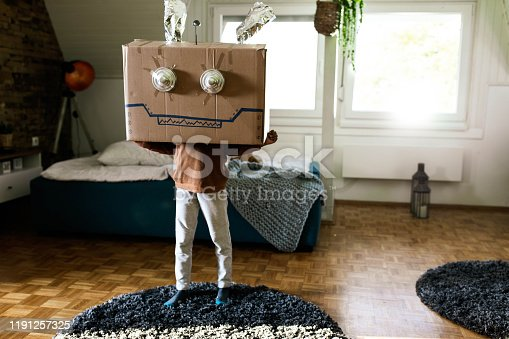 Small kid holding large cardboard box while pretending to be a robot at home.