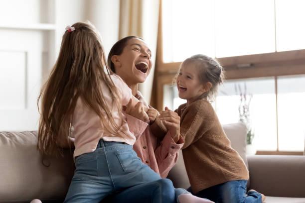Kleine Kinder Töchter kitzeln spielen mit glücklichmama auf dem Sofa – Foto