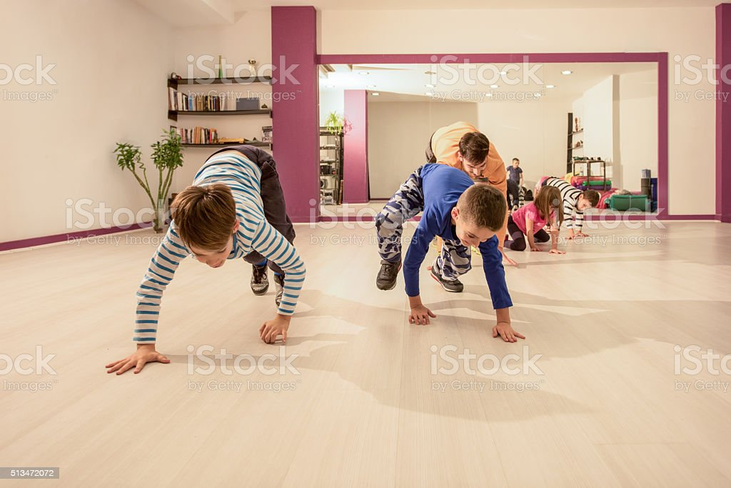 Small kids having fun with their coach on sports training. stock photo