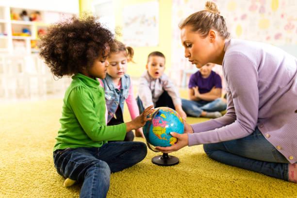 kleine kinder, die geographie-klasse im vorschulalter haben - erzieherin stock-fotos und bilder