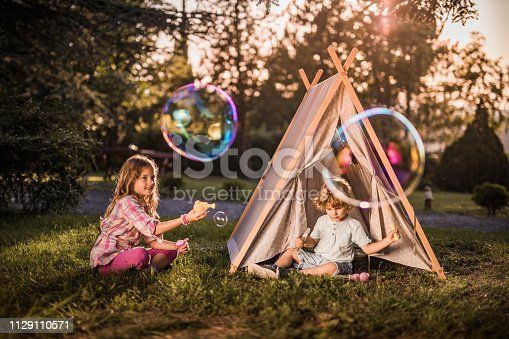 Two small siblings having fun while playing with bubble wand in nature. Little boy is sitting in front of a tent.