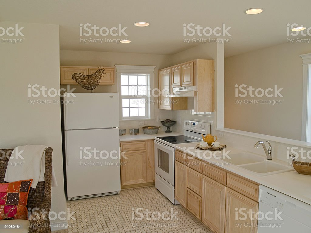 A Small Kitchen With White Appliances And Beige Walls Stock Photo