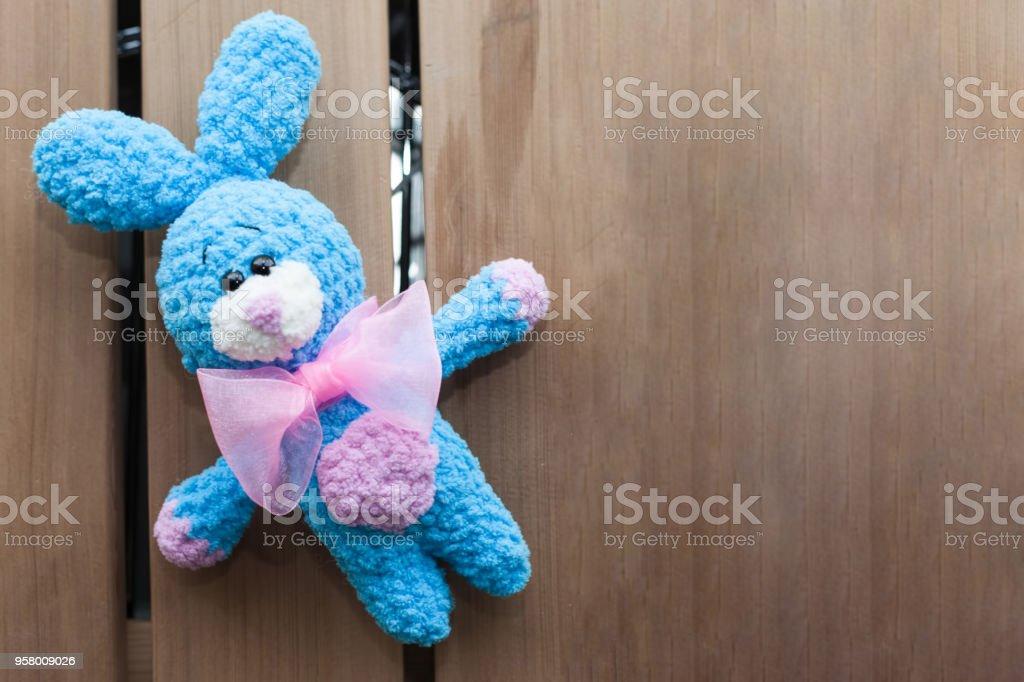 Un pequeño punto azul conejo con pajarita rosa sobre un fondo de madera vieja. Juguete de punto, hechos a mano. Amigurumi - foto de stock