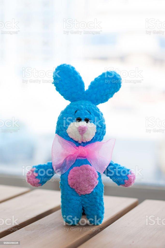 Un pequeño punto azul conejo con pajarita rosa sobre superficie de madera. Juguete de punto, hechos a mano. Amigurumi - foto de stock