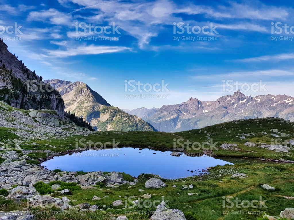 """Small lake in front of the """"Grand pic de Belledonne"""" Small natural lake scoff at the higher point of the Belledonne mountains. Awe Stock Photo"""
