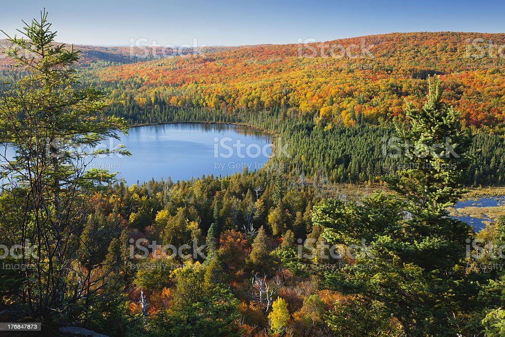 Small lake surrounded by hills with Fall color stock photo