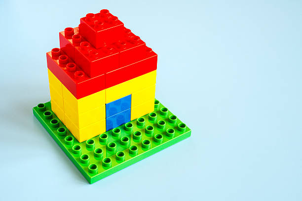 small lego house made with lego (duplo) on turquoise background. - lego house stock photos and pictures