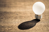 White small light bulb with shadow on wood background, Time to start success