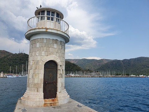 A small lighthouse in a bay by the sea.  The lighthouse serves as a signpost for sailors.