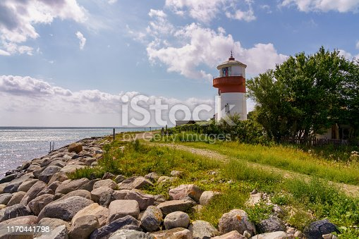 istock Small lighthouse with a footpath and the coast of the Baltic Sea on the island langeland 1170441798