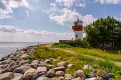 Small lighthouse with a footpath and the coast of the Baltic Sea on the island langeland