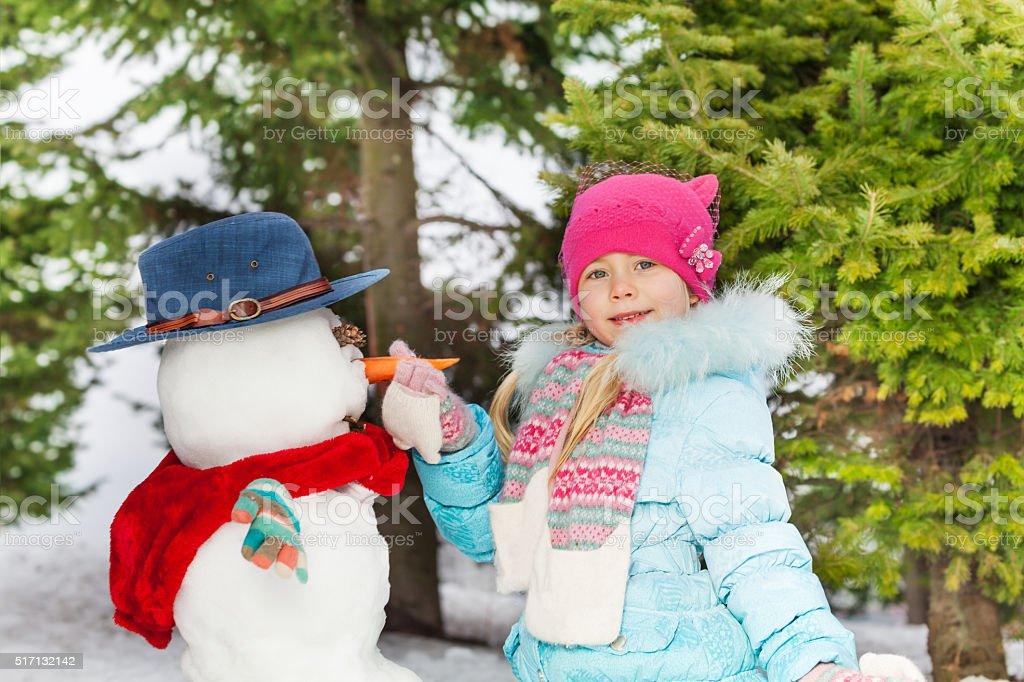 Small little girl put carrot making snowman stock photo