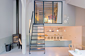 Small living room and kitchen up the stairs and dawn in fashionable loft studio apartment.