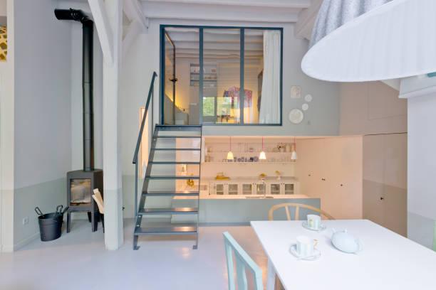 kleines wohnzimmer und küche die treppe hinauf und in der angesagten loft-studio-wohnung. - kleiner couchtisch stock-fotos und bilder